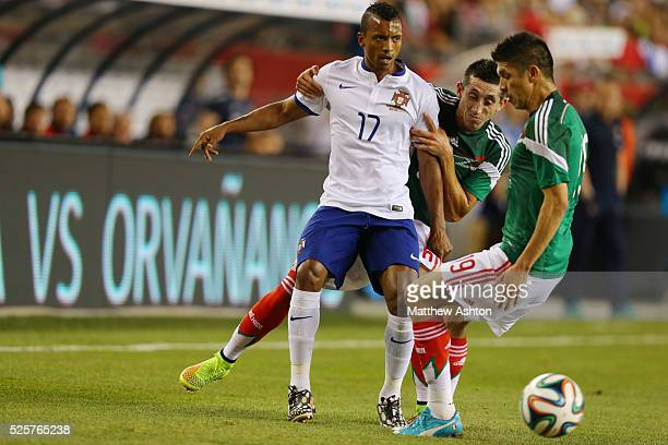 Nani of Portugal gets held back by Hector Herrera of Mexico