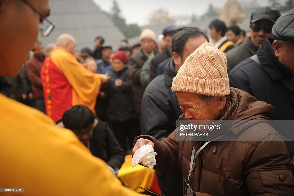 A Nanjing massacre survivor cries as a Buddhist monk bless visitors as they pay their respects with other survivors to victims on the 75th anniversary of the Nanjing massacre at the Memorial Museum in Nanjing on December 13, 2012. Air raid sirens sounded in the Chinese city of Nanjing on December 13 as it marked the 75th anniversary of the mass killing and rape committed there by Japanese soldiers -- with the Asian powers' ties at a deep low. AFP PHOTO/Peter PARKS