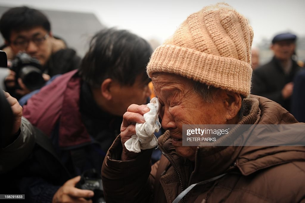 A Nanjing massacre survivor cries as she pays her respects with other survivors to victims on the 75th anniversary of the Nanjing massacre at the Memorial Museum in Nanjing on December 13, 2012. Air raid sirens sounded in the Chinese city of Nanjing on December 13 as it marked the 75th anniversary of the mass killing and rape committed there by Japanese soldiers -- with the Asian powers' ties at a deep low. AFP PHOTO/Peter PARKS
