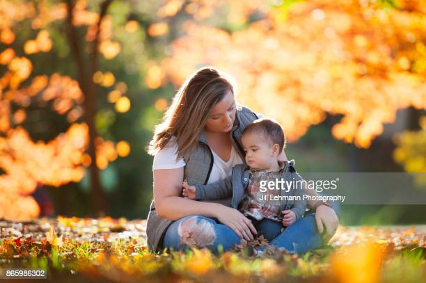 Nanny Embraces 15 Month Old Fraternal Twin at the Iowa State Campus in the Autumn Leaves full of color