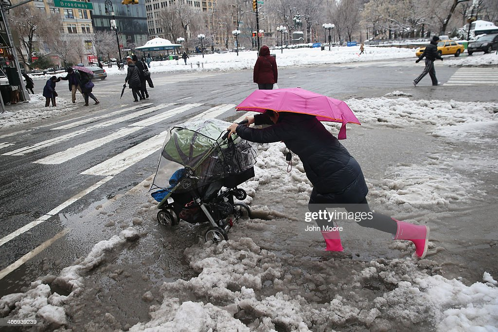 A nanny pushes a child through the slushy intersection of Broadway and 14th Street at Union Square on February 5, 2014 in New York City. New Yorkers, like millions of Americans in the northeast, dealt with the latest winter storm, which dumped 4 inches of snow on Central Park before turning to rain.