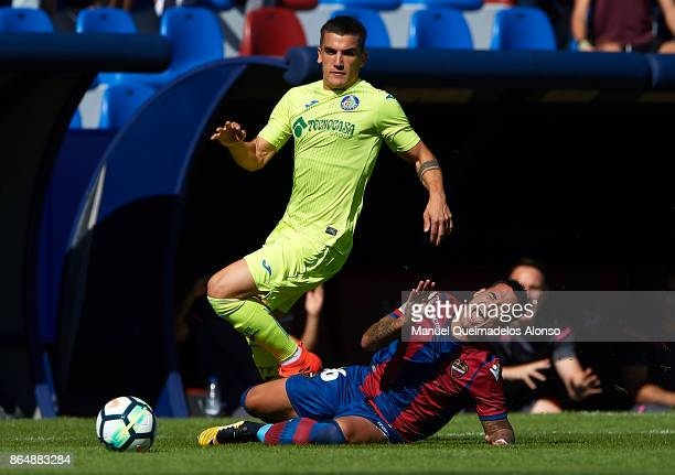 Nano of Levante is tackled by Mauro Arambarri of Getafe during the La Liga match between Levante and Getafe at Ciutat de Valencia Stadium on October...