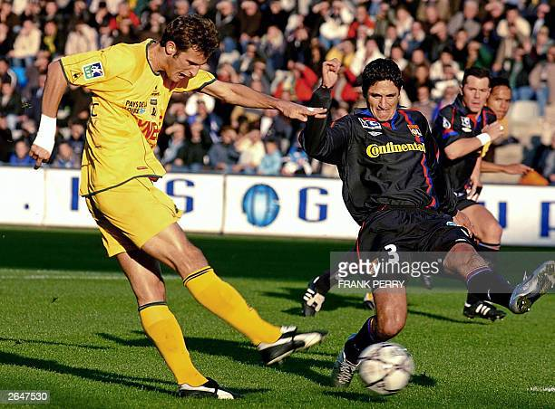 Nantes' forward Gregory Pujol vies with Lyon's Brazilian defender Edmilson 25 October 2003 during their French L1 soccer match at La Beaujoire...