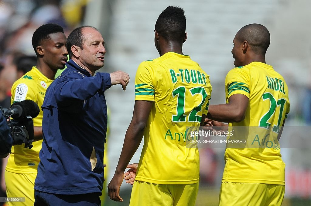 Nantes' French assistant coach Bruno Baronchelli (L) celebrates with his players after winning the French L1 football match between Nantes and Guingamp on April 13, 2014 at the Beaujoire stadium in Nantes, western France.