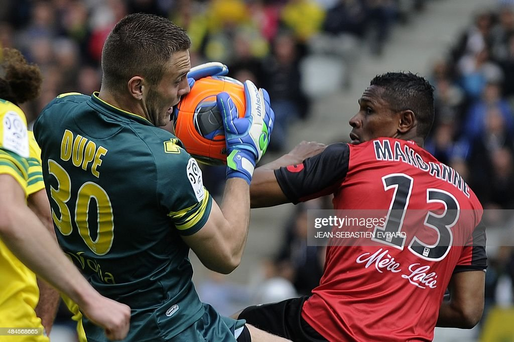 Nantes' French goalkeeper Maxime Dupe (L) vies with Guingamp's French forward Christophe Mandanne during the French L1 football match between Nantes and Guingamp on April 13, 2014 at the Beaujoire stadium in Nantes, western France.