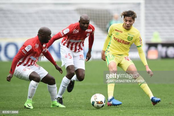 Nantes' French midfielder Amine Harit vies with Nancy's French midfielder Issiar Dia and Nancy's French defender Modou Diagne during the French L1...