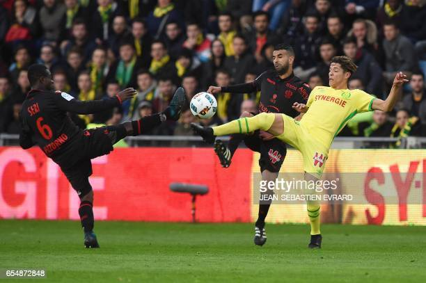 Nantes' French midfielder Amine Harit vies with Nice's French midfielder Valentin Eysseric and Nice's Ivorian midfielder Jean Michael Seri during the...