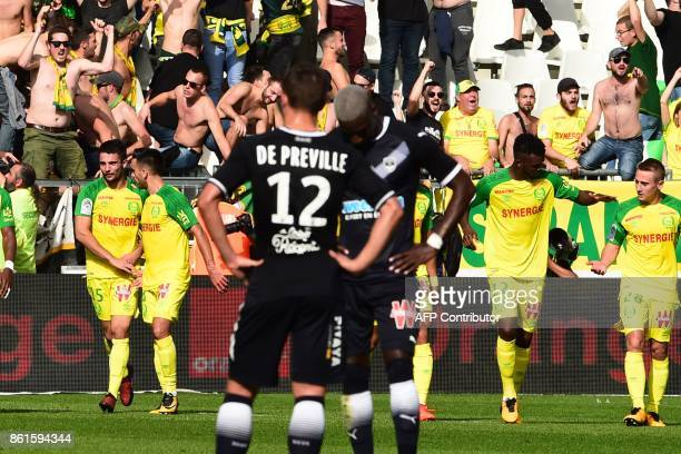 Nantes' players celebrate next to fans after scoring a goal during the French Ligue 1 football match between Bordeaux and Nantes on October 15 2017...