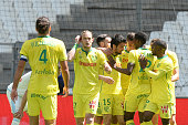 FC Nantes players greet Nantes' French defender Leo Dubois after Marseille scored an own goal following Dubois' center during the French L1 football...
