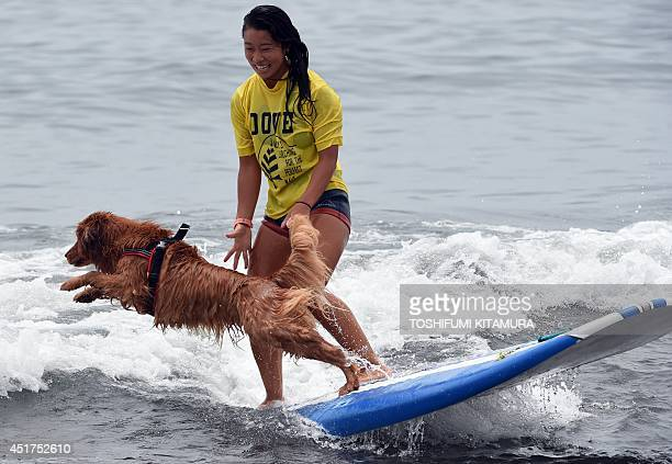 Nao Omura rides on a wave while her dog Bell jumps into the water during the animal surfing portion of the Mabo Royal Kj Cup surfing contest at...