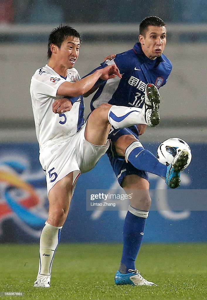 Naoki Ishikawa (L) of Vegalta Sendaion challenges Jevtic Aleksandar of Jiangsu Sainty during the AFC Champions League match between Jiangsu Sainty and Vegalta Sendai at Nanjing Olympic Sports Center Stadium on March 12, 2013 in Nanjing, China.