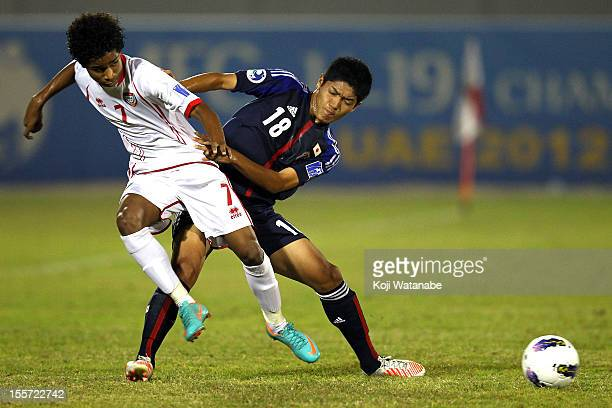 Naoki Kawaguchi of Japan and W Ambar of UAE compete for the ball during the AFC U19 Championship Group A match between the United Arab Emirates and...