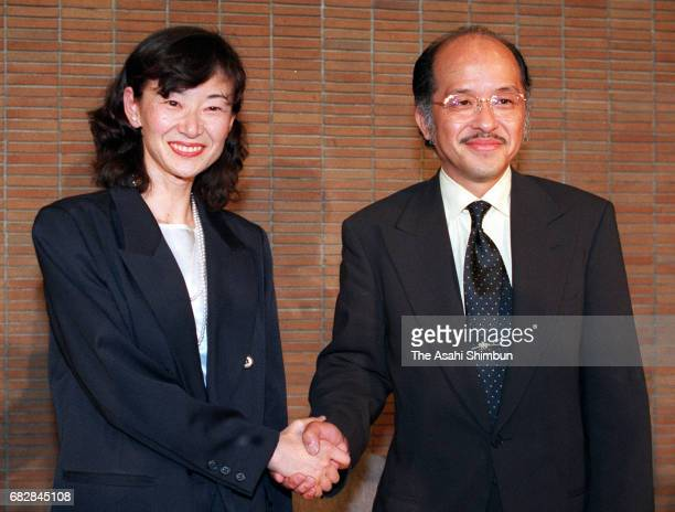 Naoki Prize laureates Setsuko Shinoda and Jiro Asada shake hands during a press conference as 117th Naoki Prize and Akutagawa Prize announced on July...