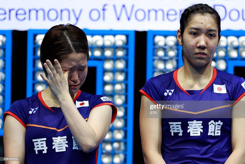 Naoko Fukuman (L) of Japan cries as her partner Kurumi Yonao of Japan stands beside her during the award ceremony of the women's doubles final match at the 2016 Badminton Asia Championships in Wuhan, central China's Hubei province on May 1, 2016. / AFP / STR