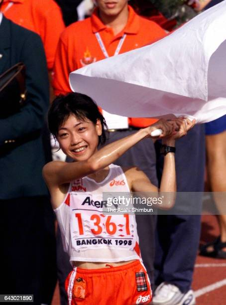 Naoko Takahashi of Japan celebrates winning the gold medal in the Women's Marathon on day zero of the 13th Asian Games at Thammasat University...