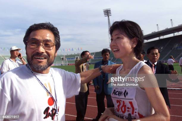 Naoko Takahashi of Japan celebrates winning the gold medal in the Women's Marathon with her coach Yoshio Koide on day zero of the 13th Asian Games at...