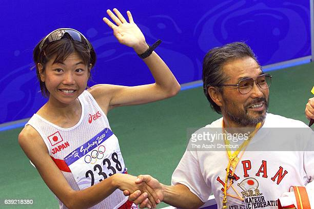 Naoko Takahashi of Japan celebrates winning the gold medal with her coach Yoshio Koide after the Women's Marathon during the Sydney Olympics at...