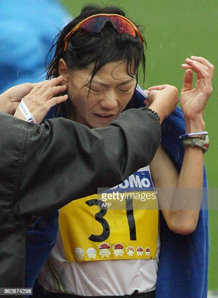 Naoko Takahashi of Japan is helped by an official after crossing the finish line in the Tokyo international women's marathon in Tokyo 19 November...
