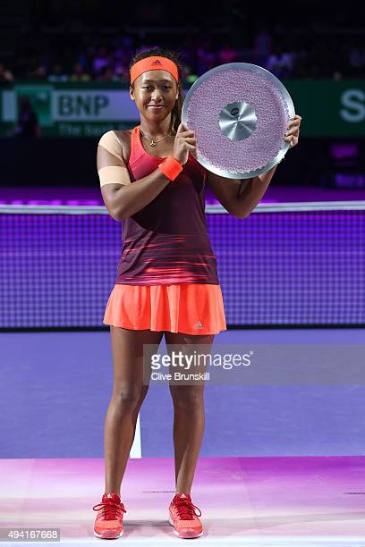 Naomi Osaka of Japan holds the winners trophy after defeating Caroline Garcia of France during the WTA Rising Stars Final at Singapore Sports Hub on...