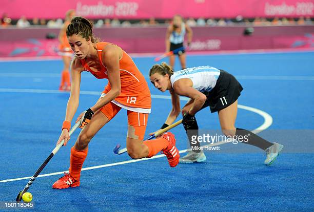 Naomi Van As of Netherlands controls the ball against Carla Rebecchi of Argentina during the Women's Hockey gold medal match on Day 14 of the London...