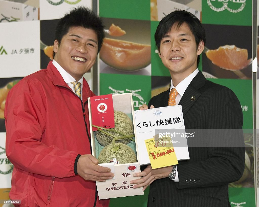 Naomichi Suzuki (R), mayor of the Hokkaido city of Yubari, holds a pair of Yubari melons with Takamaru Konishi, buyer at a supermarket in Amagasaki, western Japan, who became the winning bidder of the premium melons with a record-setting price of 3 million yen in the season's first auction in Sapporo on May 26, 2016.
