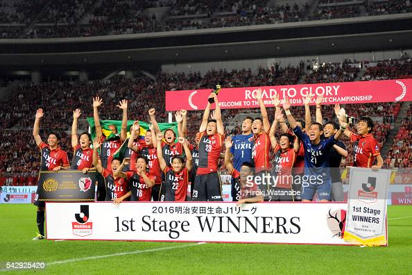 Naomichi Ueda of Kashima Antlers lifts the trophy as they celebrate JLeague first stage champion after their 20 win in the JLeague match between...