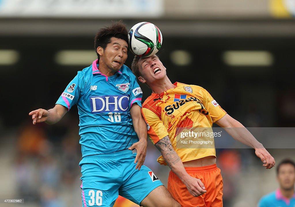 Naoya Kikuchi of Sagan Tosu and Mitchell Duke of Shimizu S-Pulse compete for the ball during the J.League match between Shimizu S-Pulse and Sagan Tosu at IAI Stadium Nihondaira on May 6, 2015 in Shizuoka, Japan.