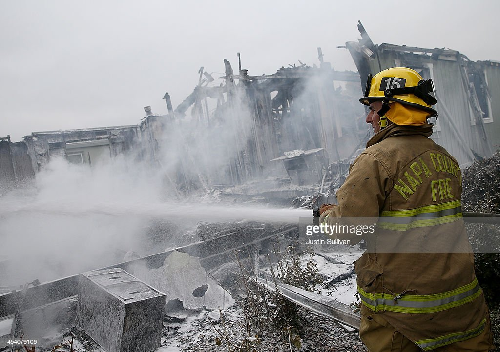 A Napa County firefighter sprays foam on hot spots from a fire at a mobile home park following a reported 6.0 earthquake on August 24, 2014 in Napa, California. A 6.0 earthquake rocked the San Francisco Bay Area shortly after 3:00 am on Sunday morning causing damage to buildings and sending at least 70 people to a hospital with non-life threatening injuries.