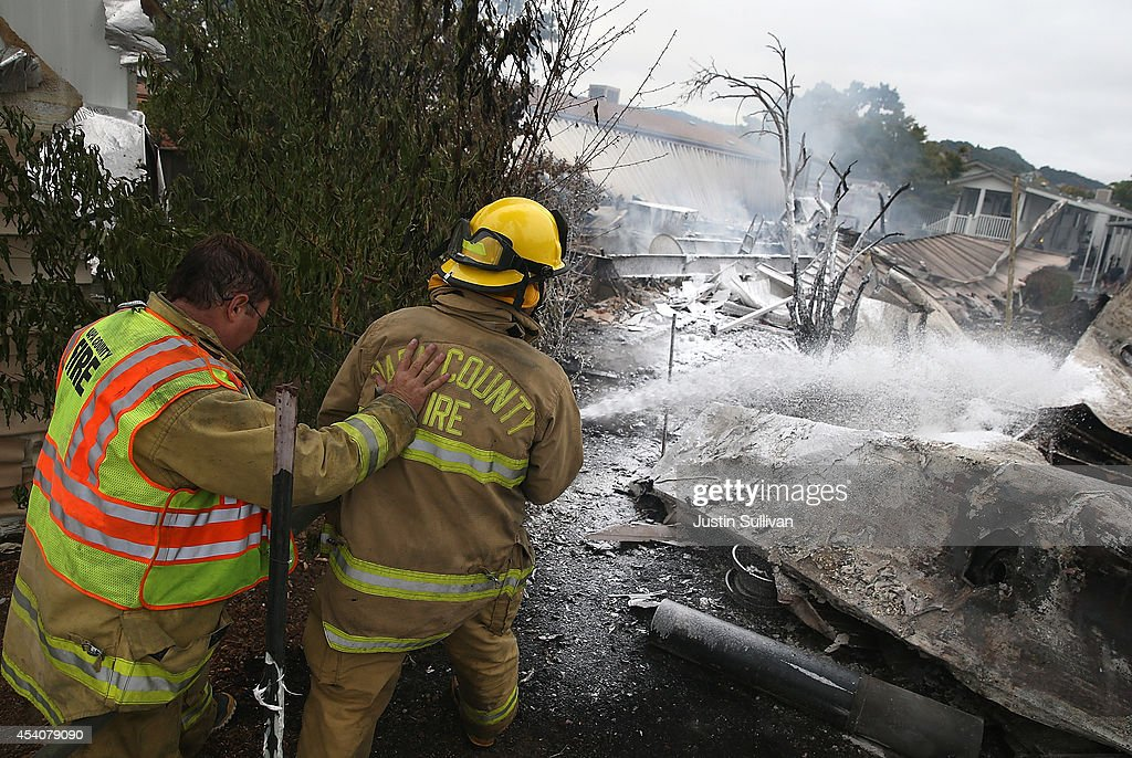 Napa County firefighters spray foam on hot spots from a fire at a mobile home park following a reported 6.0 earthquake on August 24, 2014 in Napa, California. A 6.0 earthquake rocked the San Francisco Bay Area shortly after 3:00 am on Sunday morning causing damage to buildings and sending at least 70 people to a hospital with non-life threatening injuries.