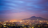Naples (Napoli, Campania, Italy) By Night With Volcano Vesuvio as background. Long exposure, city traffic lights and clouds in motion.