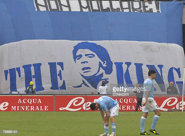 Football player trains past a giant banner depicting soccer star Diego Arnando Maradona and reading 'The King' and ' resist ' in the San Paolo...