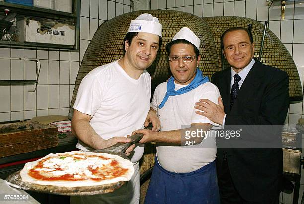 Former Italian Prime Minister Silvio Berlusconi poses with pizzaioli during an electoral rally in Naples 19 May 2006 Silvio Berlusconi comes at the...