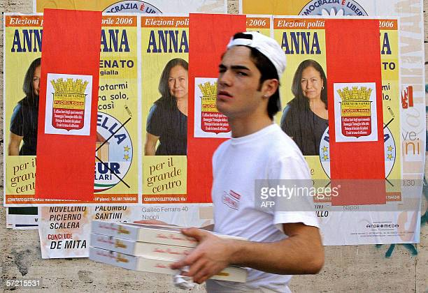 Pizza's delivery man passes by electoral posters in Naples 30 March 2006 10 days before the Italian general elections The last opinion polls before...