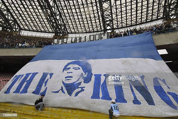 Two supporters help to set up a giant banner depicting soccer star Diego Arnando Maradona as 'The King' and a small one above reading ' resist ' in...