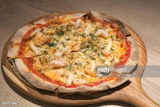 Naples seafood pizza put on a wood table