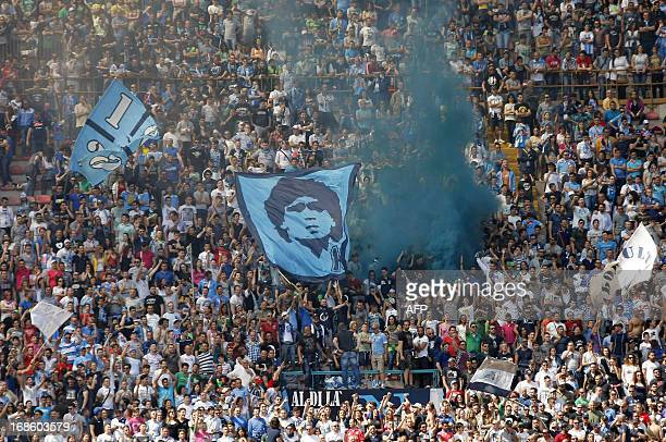 Naples supporters hold up a flag with a portrait of former Napoli player and football legend Diego Armando Maradona during the Serie A football match...