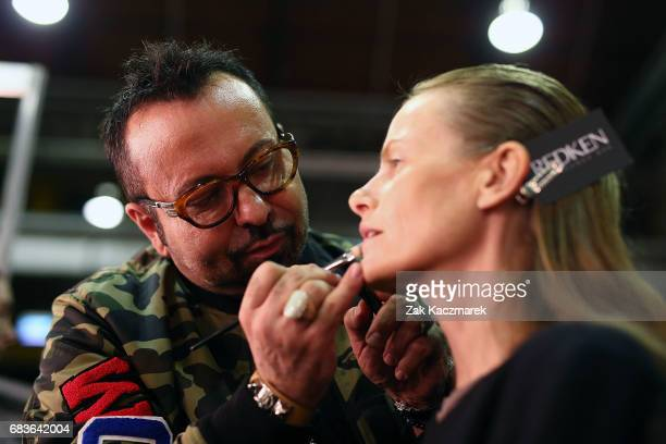 Napoleon Perdis applies the finishing touches as a model prepares backstage ahead of the Christopher Esber show at MercedesBenz Fashion Week Resort...