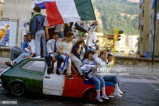 Napoli fans celebrate winning the league title by sitting on a car which has the Italian flag painted on it