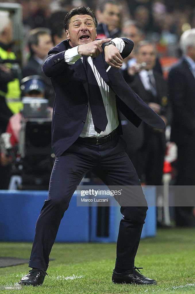 Napoli manager Walter Mazzarri gestures to his watch during the Serie A match between AC Milan and SSC Napoli at San Siro Stadium on April 14, 2013 in Milan, Italy.
