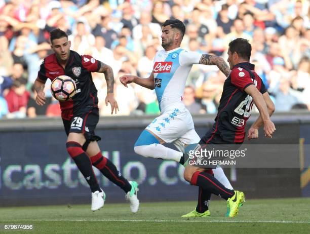 Napoli's Albanian defender Elseid Hysaj fights for the ball with Cagliari's Italian defender Nicola Murru and Cagliari's Italian midfielder Simone...
