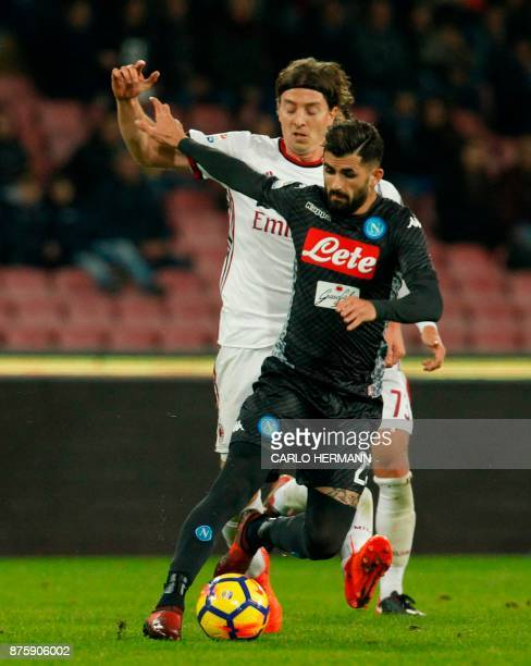 Napoli's Albanian defender Elseid Hysaj fights for the ball with Milan's Italian midfielder Riccardo Montolivo during the Italian Serie A football...
