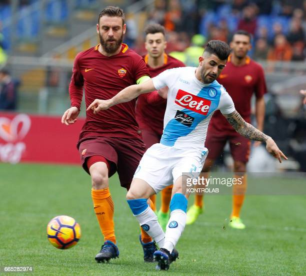 Napoli's Albanian defender Elseid Hysaj fights for the ball with Roma's Italian midfielder Daniele De Rossi during the Italian Serie A football match...