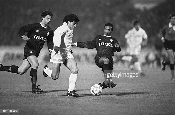 Napoli's Argentine star player Diego Maradona tries to avoid Bordeaux's Jean Tigana's tackle 23 November 1988 as Alain Roche looks on during their...