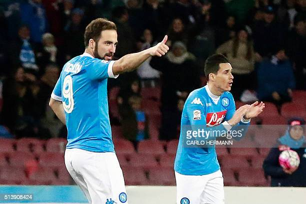 Napoli's Argentinian forward Gonzalo Higuain celebrates after scoring as his teammate Napoli's Spanish forward Jose Maria Callejon gestures during...