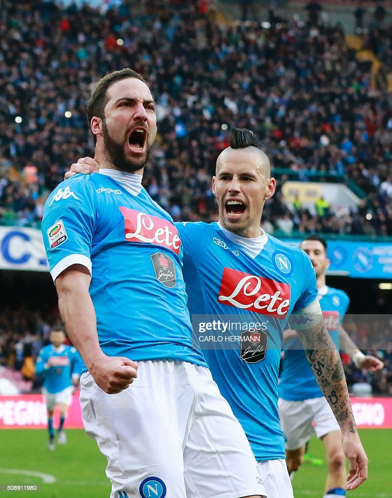 Napoli's Argentinian-French forward Gonzalo Higuain (L) celebrates after scoring with midfielder Marek Hamsik during the Italian Serie A football match SSC Napoli vs Carpi FC on February 7, 2016 at the San Paolo stadium in Naples. / AFP / CARLO HERMANN
