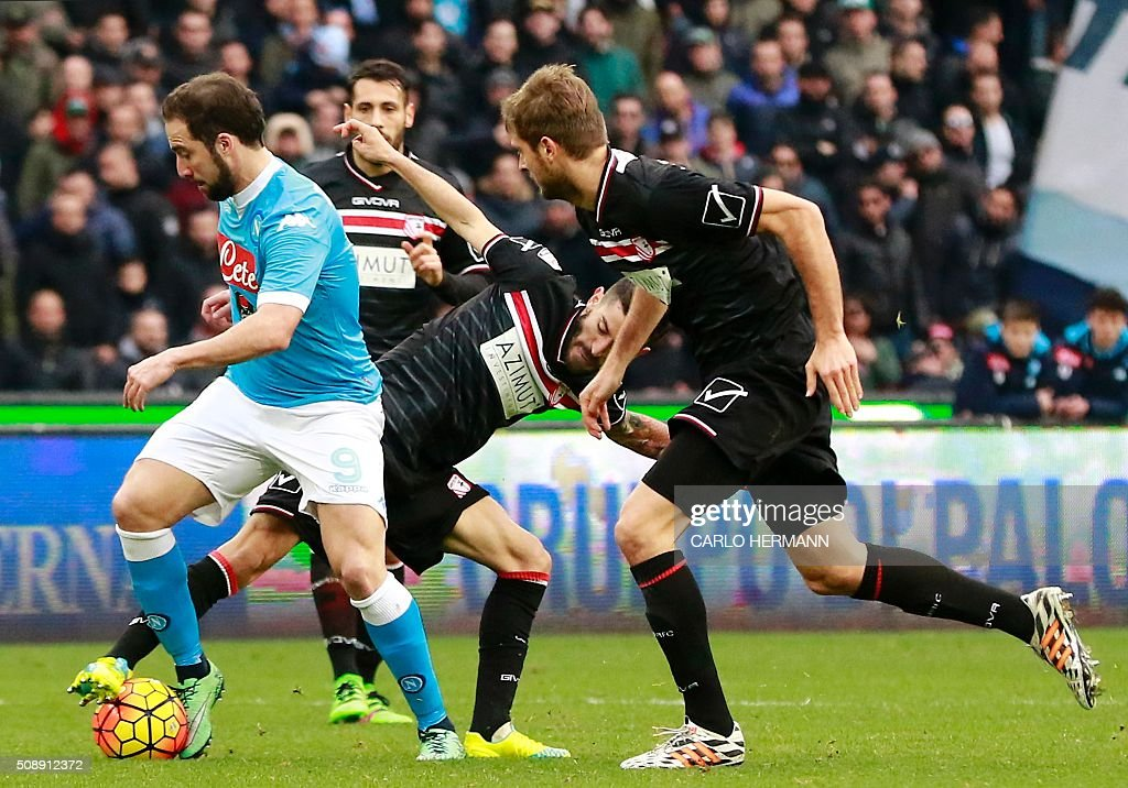 Napoli's Argentinian-French forward Gonzalo Higuain (L) vies with Carpi's Italian midfielder Marco Crimi (C) and Carpi's Italian defender Simone Romagnoli during the Italian Serie A football match SSC Napoli vs Carpi FC on February 7, 2016 at the San Paolo stadium in Naples. / AFP / CARLO HERMANN