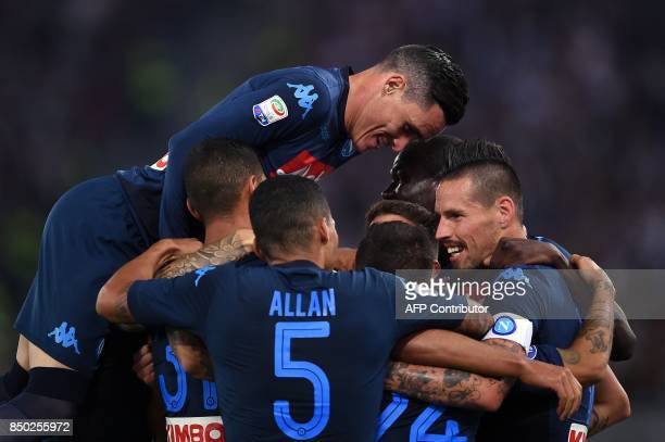 Napoli's Belgian forward Dries Mertens is celebrated by teammates after scoring during the Italian Serie A football match between Lazio and Napoli at...