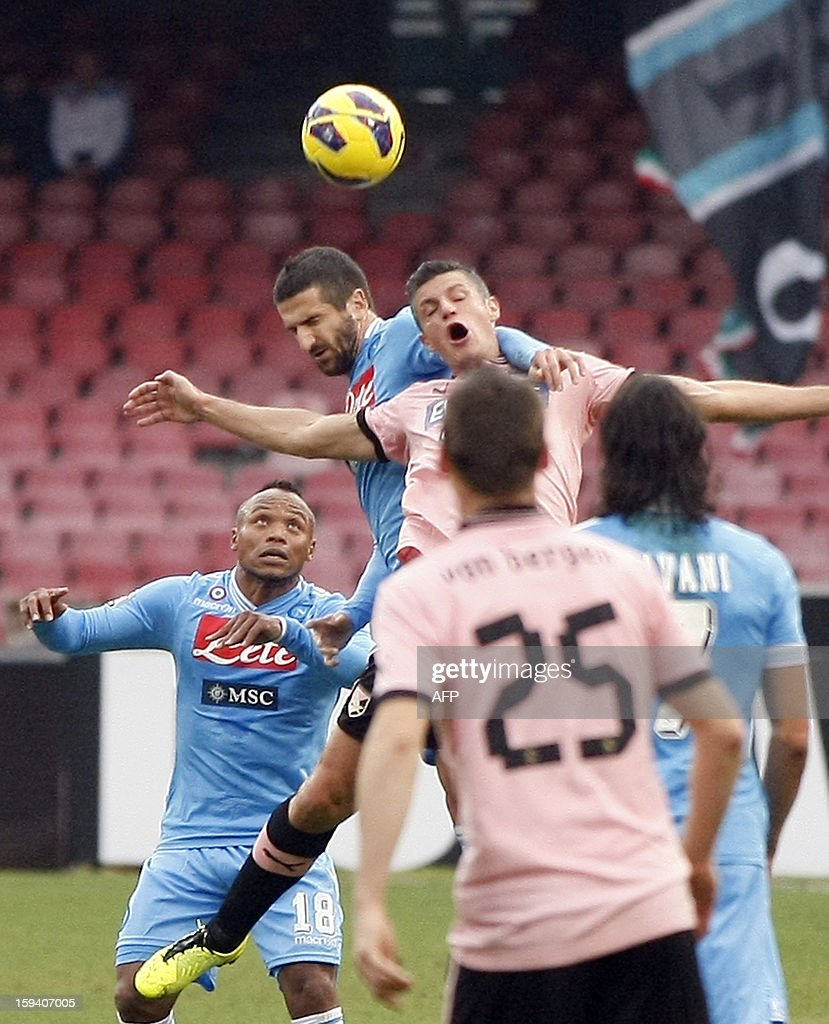 Napoli's defender Alessandro Gamberini (2nd L) jumps for the ball next to Palermo's defender Michel Morganella during the Italian Serie A football match SSC Napoli vs US Palermo won by SSC Napoli 3-0 at San Paolo Stadium in Naples on January 13, 2013. AFP PHOTO / CARLO HERMANN