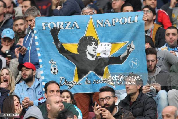Napoli's fans hold a flag showing Argentinian football star Diego Maradona before the Tim Cup semifinal second leg football match SSC Napoli vs...
