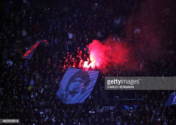 Napoli's fans holds a flag with the face of the former Argentinian football player Diego Armando Maradona as the burn flares during the Italian Serie...